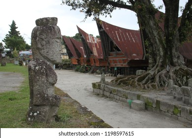 stone idol in a village on the island of Samosir on the background of traditional wooden houses