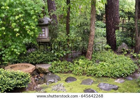 A Stone Lantern And Birdbath In The Shrubs In A Japanese Garden