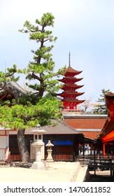 Stone lanterns in temple yard and Goju-no-to pagoda (Gojunoto pagoda, Five storied pagoda) of Itsukushima Shrine, sacred Miyajima Island, Japan