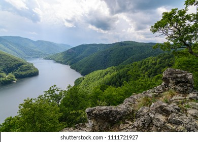 Stone lookout to a lake and green forested hills in Europe, Romania at Tarnita lake, a place named Dan's stone, Piatra lui Dan