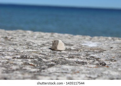 Stone lying on a small rock plate with sea view at the back