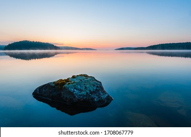 Stone lying in still lake at sunrise