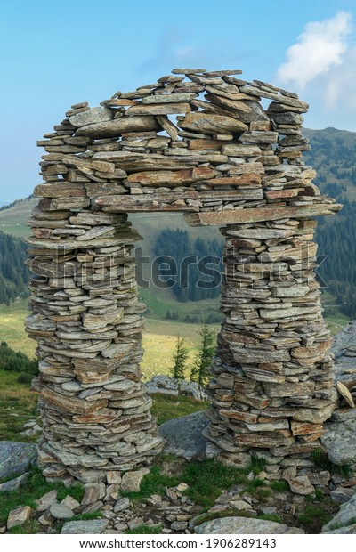A stone made window, with the view on Packalpen, Austrian Alps. The stones are placed by humans, creating towers. The mountains around are lush green. Clear and bright day. Outdoor activity