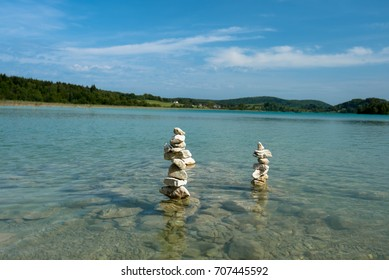Stone manniquins at the  lake Illay in the French Jura region