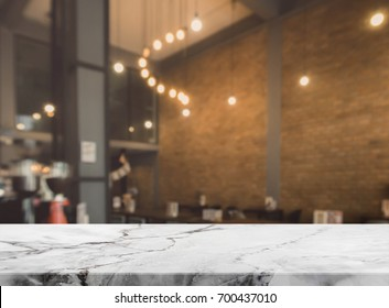 Stone marble table top and blurred bokeh cafe and coffee shop interior background with vintage filter - can used for display or montage your products.