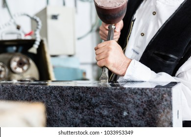 Stone mason working on tombstone in his workshop