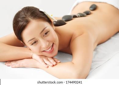 Stone Massage. Beautiful Woman Getting Spa Hot Stones Massage in Spa Salon.
