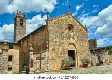 Stone, medieval church with a bell tower in the village of Monteriggioni in Toscana, Italy