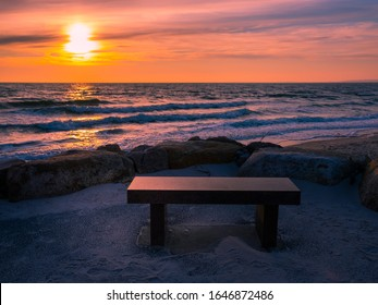 Stone memorial bench near beach at sunset