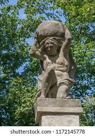 Stone men figure carrying stone, baroque statue from Greek mythology of Sisyphus or Sisyphos