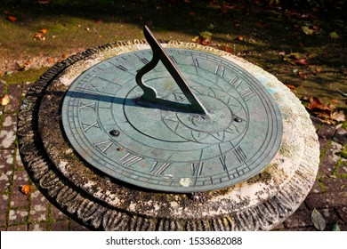 Stone and metal garden sundial on a mottled brick garden path