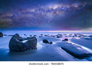 Stone with milkyway background at Moeraki Boulders, New Zealand.