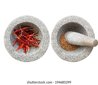 stone mortar and pestle, with chili and peppercorn inside.