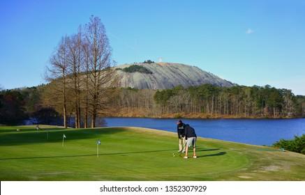 STONE MOUNTAIN, GEORGIA, USA - MARCH 19, 2019: Lakeside golf. Golf players at Stone Mountain Golf Club, in the background historic Stone Mountain Summit.