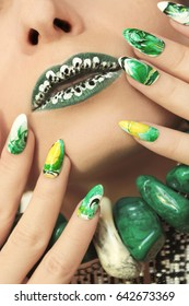 Stone nail design in white and green colors with veins of dark and yellow color nail Polish on a sharply oval-shaped nails closeup.Nail art.