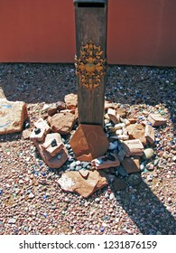 Stone Ohm stone against decorated wood post in high desert.