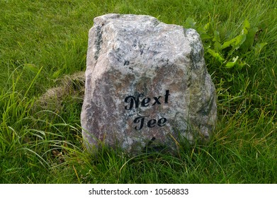 stone on a grass field with a carving saying next tee (golf sport)