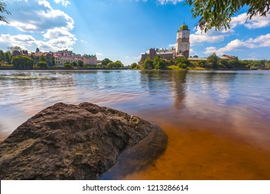 The stone on the shore of the Vyborg Bay in the clear water against the backdrop of the tower of St. Olaf opposite the modern colorful buildings of the city. Medieval Vyborg Castle, Russia.