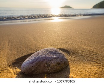 A stone on a Thai beach at sunset casts a show