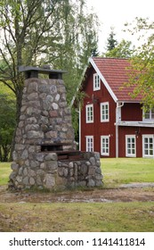 A stone oven for glass blowing purpose in autumn in front of a blurred out traditional red and white Scandinavian house in Smaland, Sweden