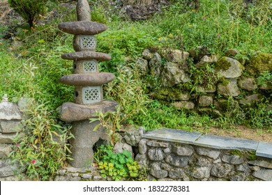 Stone pagoda against green foliage next to stone wall.