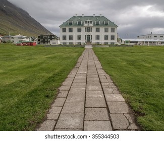 Stone path leading up to large white house in Isafjordur Iceland on a cloudy day.