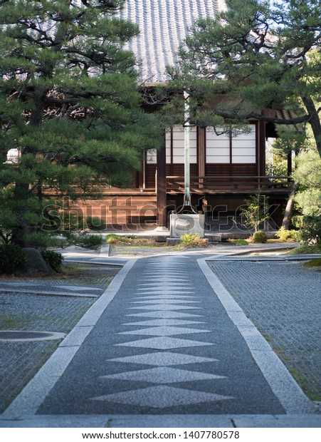 Stone path leading to a quiet temple in Kyoto, Japan. Under the water pipe: Senmatsuzan (part of the temple name)