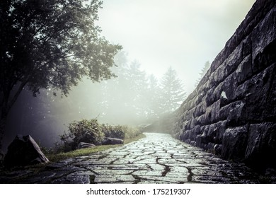 A stone path and wall in what appears to be fog but is actually a cloud rolling over a mountain
