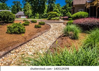 Stone path winds through a garden area beside a high-end villa