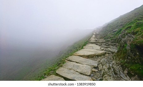 Stone pathway disappearing to vanishing point with drop over edge into fog high up at narrow point on PYG trail on Mount Snowdon in Snowdonia National Park, Wales, UK