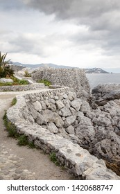 stone pathway going along the coastline of spain