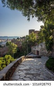 Stone pathway leading down the hill overlooking Malaga, Spain, Europe with trees on either side on a bright summer day