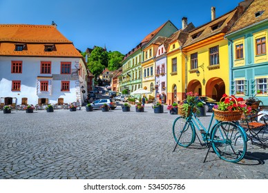 Stone paved old street and cafe bar with colorful retro buildings in city center, Sighisoara fortress, Transylvania, Romania, Europe