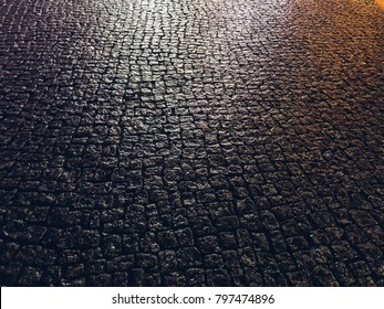 Stone pavement in perspective. Stone pavement texture. Granite cobblestoned pavement background. Abstract background of a cobblestone pavement close-up, wet