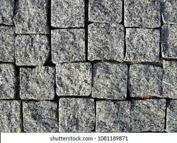 Stone pavement texture, granite cobblestoned pavement background, cobbled stone road regular shapes, abstract background of old cobblestone pavement close-up.