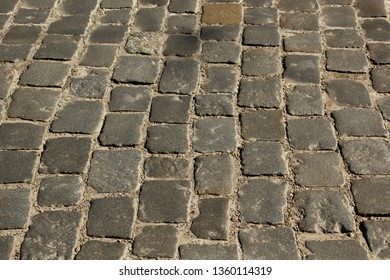 Stone pavement texture. Granite cobblestoned pavement background. Abstract background of old cobblestone pavement close-up. Seamless texture.