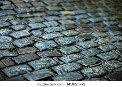 Stone pavement texture. Granite cobblestoned pavement background.  Cobbled stone road regular shapes, abstract background of old cobblestone pavement close-up.