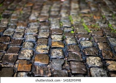 Stone pavement texture. Granite cobblestoned pavement background.  Cobbled stone road regular shapes, abstract background of old cobblestone pavement close-up.