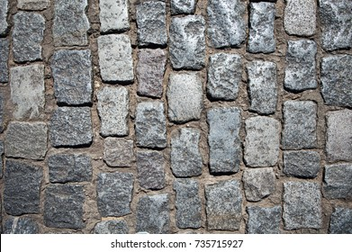 Stone pavement texture, granite cobblestoned pavement background, cobbled stone road regular shapes, abstract background of old cobblestone pavement close-up