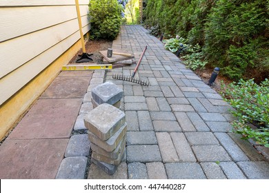 Stone Pavers and tiles for side yard patio hardscape with garden landscaping tools rubber mallet sand gravel tamper level rake