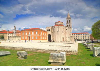 Stone pieces from ancient Roman forum and distant church building in Zadar, Croatia