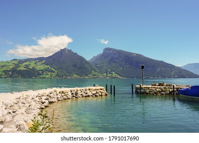 Stone pier on a calm lake with mountain backdrop and clear blue sky