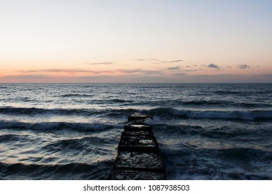 Stone pier in the sea on a sunrise