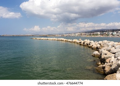 Stone pier stretching into the sea on the background of the old town
