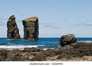 Stone pillars in the Atlantic Ocean. Massive natural monument made of lava stone.