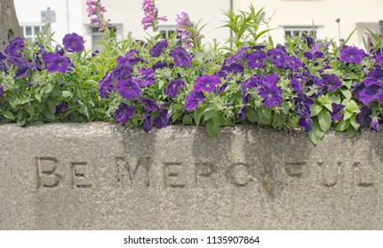 A stone plant container with be merciful engraved