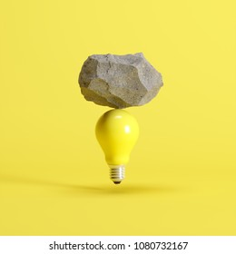 Stone put on yellow light bulb floating on yellow background. minimal creative idea concept.