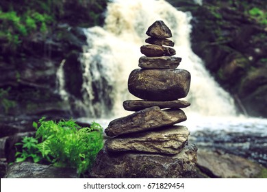 Stone pyramid near a tropical waterfall. The concept of harmony and balance.