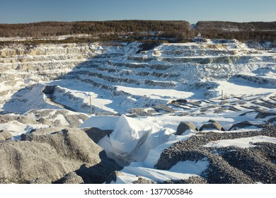 Stone quarry covered with snow in a winter sunny day.
