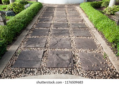 Stone and rock walkway in the garden decorated by cement edge and green plant